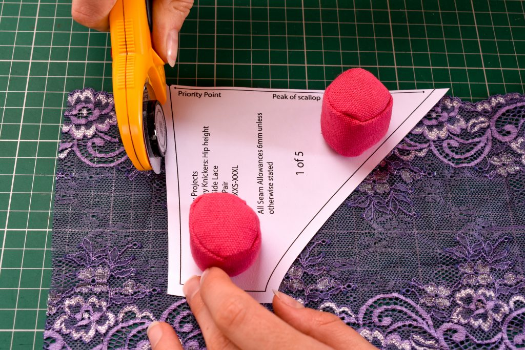 cutting out scalloped edge lace for lingerie sewing pattern with rotary cutter using pink prym fixing weights